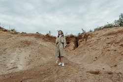 Beautiful Asian girl in a beige trench coat posing in front of sand quarry on a gloomy autumn day. Horizontal image.