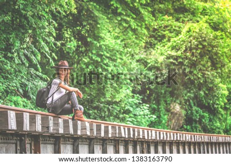 Beautiful Asian girl in casual wear with cowgirl hat sitting on rail, adventure and outdoor concept