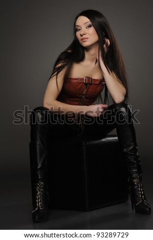 Beautiful asian girl in leather pants and corset sitting on  black cube