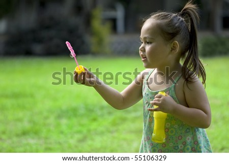 Beautiful Asian girl in summer dress trying to blow soap bubbles - stock photo