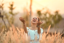 beautiful asian girl in white dress and happy Emotional in meadow by Play Grass flowers. by relax holiday in sunset light shine.