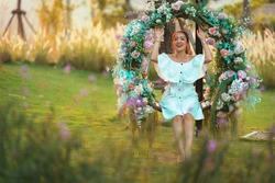 beautiful asian girl in white dress and posing relax on flower swing with blur background meadow. by relax holiday in sunset light shine. by Freedom concept