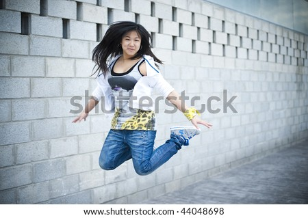 Beautiful asian girl jumping in hip hop clothes