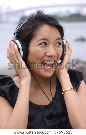 Beautiful Asian girl listening to music with her headphones