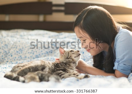Beautiful asian girl lying with american shorthair cat on the bed