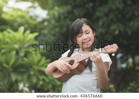 Beautiful asian girl playing ukulele, Outdoor portrait