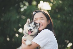 Beautiful asian girl playing with siberian husky puppy in the park with bokeh background