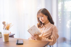 Beautiful Asian girl relaxing studying reading book casual free time weekend at café drinking coffee, social distancing feeling sad loneliness bored upset tired sleepy anxious, sitting chill careless