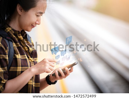 Beautiful asian girl Standing waiting for the train And she is using smartphone To find information on tourism. Travel and tourism concept.social media. #1472572499