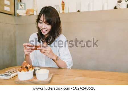 Beautiful Asian girl taking photo of chocolate toast cake, ice-cream, and milk at coffee shop. Dessert or food photograph hobby. Smartphone or mobile phone photography habit concept. With copy space
