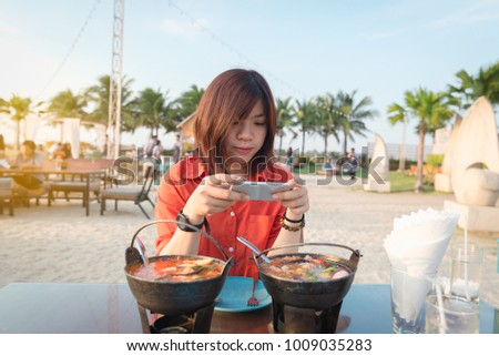 Beautiful Asian girl taking photo of thai food at restaurant