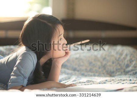Beautiful asian girl thinking on the bed