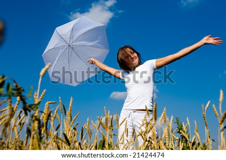 Beautiful asian girl under blue sky with umbrella in the field.