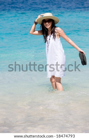 beautiful asian girl wearing hat on beach