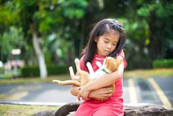 Beautiful Asian girl wearing red chipao carrying a cat in her arms.Little female with plait hair.Feline with green collar and bell.Mother Siamese cat with blue eye and exposed teats.