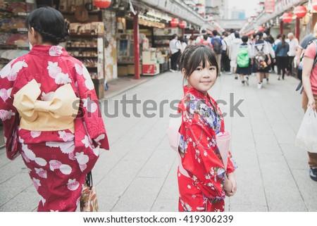 Beautiful Asian girl wearing red kimono  walking in the city,Asakusa Tokyo Japan.