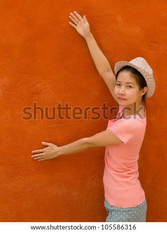Beautiful asian girl with orange concrete wall