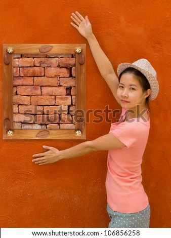 Beautiful asian girl with wooden frame and brick on orange  concrete wall