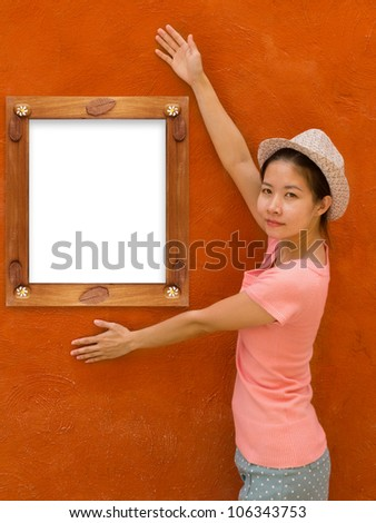 Beautiful asian girl with wooden frame on orange  concrete wall