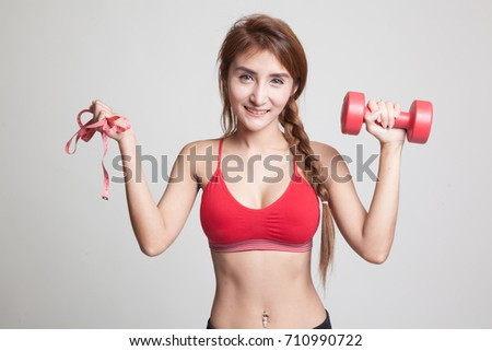Beautiful Asian healthy girl with dumbbell and measuring tape on gray background #710990722