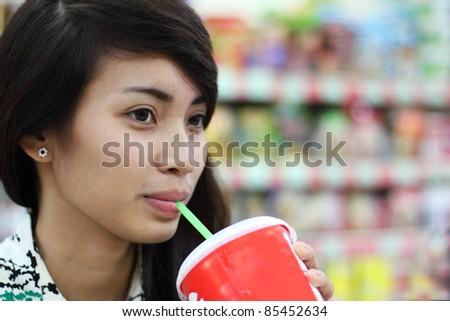 Beautiful asian lady enjoying a soda inside a grocery. - stock photo