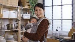 beautiful asian millennial woman holding baby in arms is experiencing pure joy as a new mother while standing in home kitchen