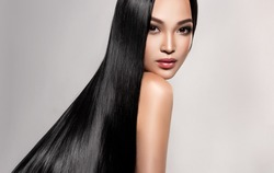 Beautiful asian model girl with shiny black and straight long hair . Keratin straightening . Treatment, care and spa procedures for hair . Chinese girl with smooth hairstyle