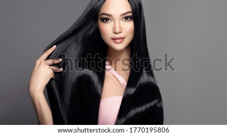 Beautiful asian model girl with shiny black and straight long hair . Keratin straightening . Treatment, care and spa procedures for haired . Chinese girl with smooth hairstyle