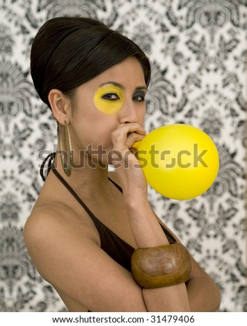 stock photo : Beautiful asian model with funky make-up blow balloon