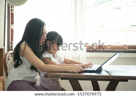 Beautiful asian mother and daughter working together at home office by the window. in concept of single mom or single parent.