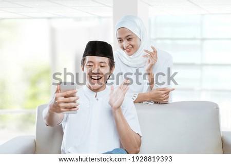 beautiful asian muslim couple making video call to talk relative during eid mubarak