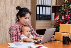 Beautiful Asian single mother woman and baby working at home using laptop, smartphone checking package products, small business startup entrepreneur, freelance lifestyle shopping online holiday season