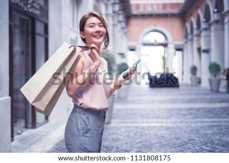 Beautiful Asian Thai girl in shopping.Happy woman with shopping, girls holding shopping bags using a smart phone and smiling while standing outdoors enjoying in shopping.Consumerism,lifestyle concept.