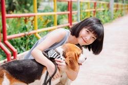 Beautiful asian thai short hair woman petting beagle dog with love. Walk the dog.
