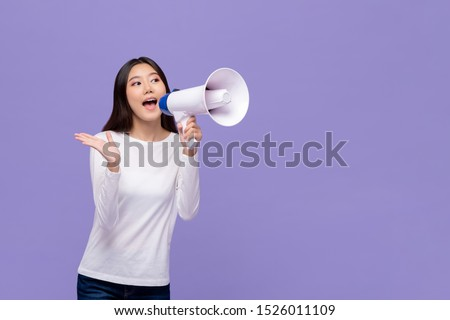 Beautiful Asian woman announcing on magaphone isolated on purple background with copy space