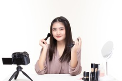 Beautiful asian woman blogger how to make up and use cosmetics. Happy asian girl vlogger recording video by camera share on social media on white background. Asia blogger or Vlogger product.