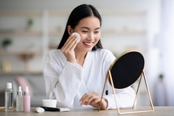 Beautiful asian woman cleaning her face, using cotton pads and cleansing product, looking at mirror in bedroom. Young attractive korean lady using face toner and cotton pad, home interior, empty space