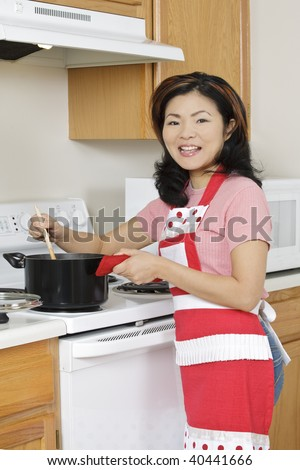 Beautiful Asian woman cooking a large pot of stew on the stove