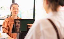 Beautiful Asian woman customer orders coffee while barista making order on cashier screen at coffee bar, face of barista appears on cashier screen. Barista work at coffee bar and food service business