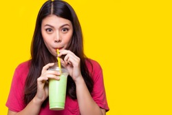 Beautiful asian woman drink iced green tea, make her refreshing in summer season. Attractive beautiful girl use straw for drinking iced green tea. She hold plastic cup. yellow background, copy space