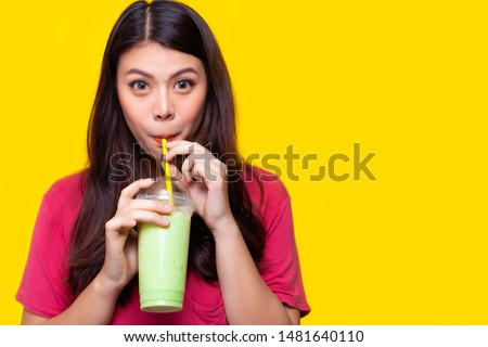 Beautiful asian woman drink iced green tea, make her refreshing in summer season. Attractive beautiful girl use straw for drinking iced green tea. She hold plastic cup. yellow background, copy space Stock photo ©