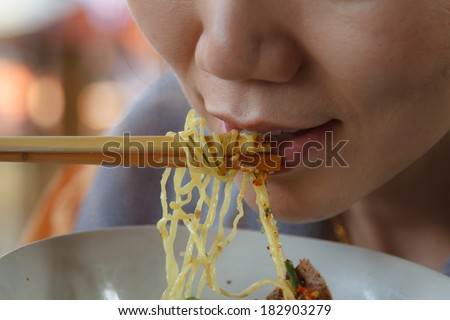 Beautiful Asian woman eating noodles with spicy.
