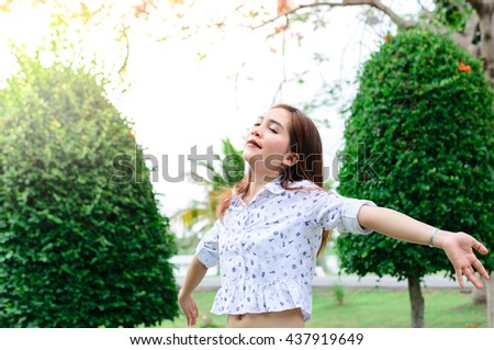 Beautiful asian woman feel fresh in the morning with bright sunlight in park