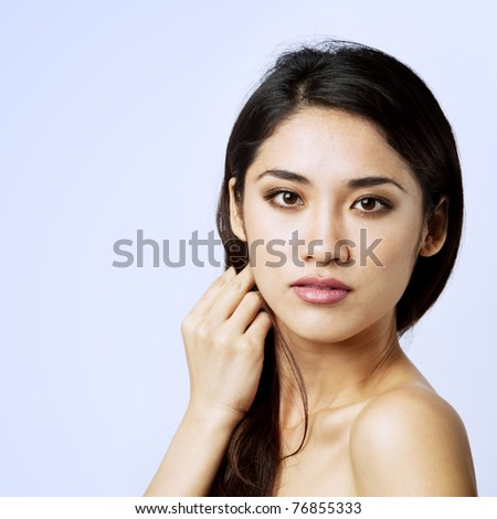 Beautiful Asian woman gently touching her face.