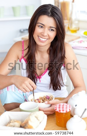 Beautiful asian woman having breakfast smiling at the camera sitting in the kitchen at home