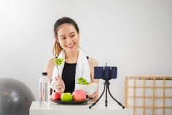 Beautiful asian woman healthy blogger is showing apple fruit and clean diet food. In front of smartphone to recording vlog video live streaming at home.Fitness influencer on social media online.