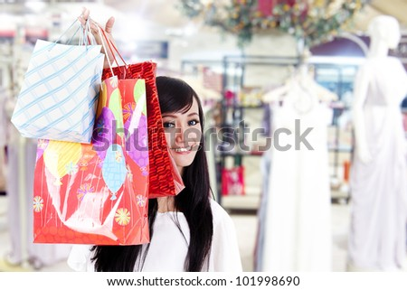 Beautiful Asian woman hides behind her shopping bags shot in shopping mall