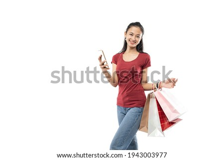Beautiful asian woman holding a shopping bag and phone posing while staring at the camera with smiling expression ストックフォト ©