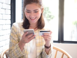 beautiful asian woman holding mobile and credit card in her hands with smiley face. Online shopping concept.