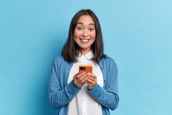 Beautiful Asian woman holds modern cellular glad to surf in social networks smiles positively dressed in casual jumper poses against blue background. Technology and online communication concept